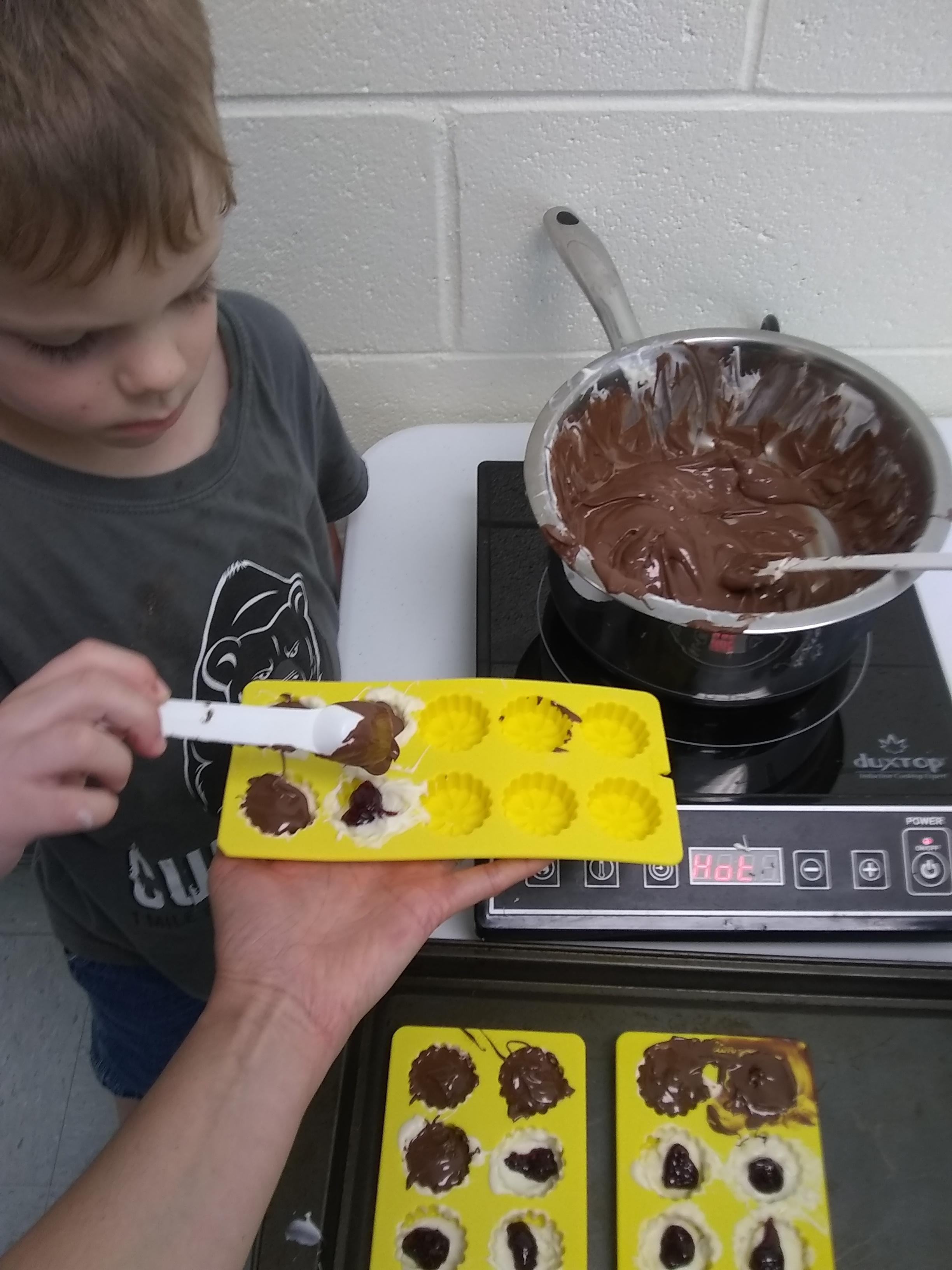 kids preparing chocolate candy shapes together