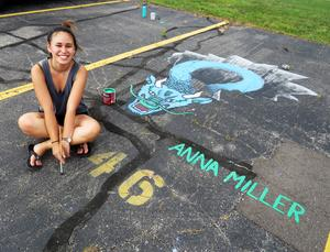 Anna Miller is putting the finishing touches on her optical illusion dragon popping out of a hole in the asphalt.