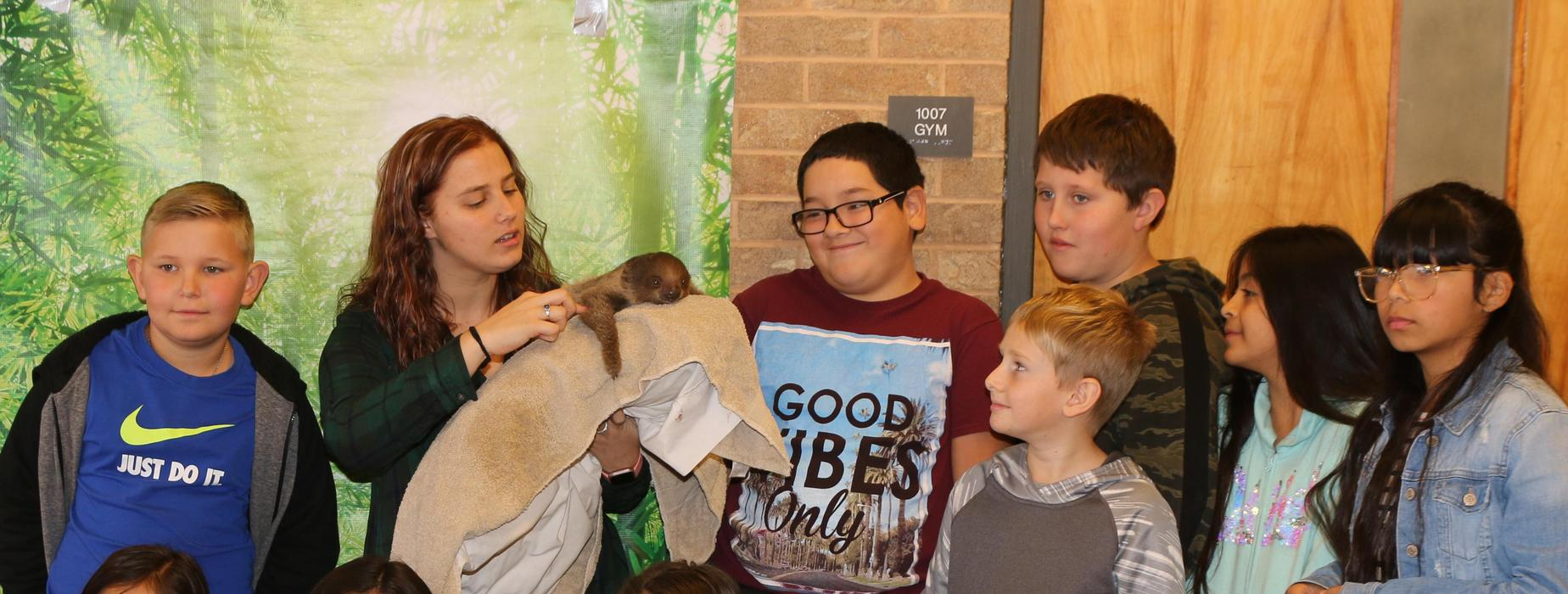 Teacher and students with a sloth.