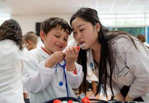 First-year COMP student Katrina Ngo goes over medical equipment with La Verne Science & Technology Charter school kindergarten student Athen Lopez during Mini-Medical School. (Jeff Malet, WesternU)