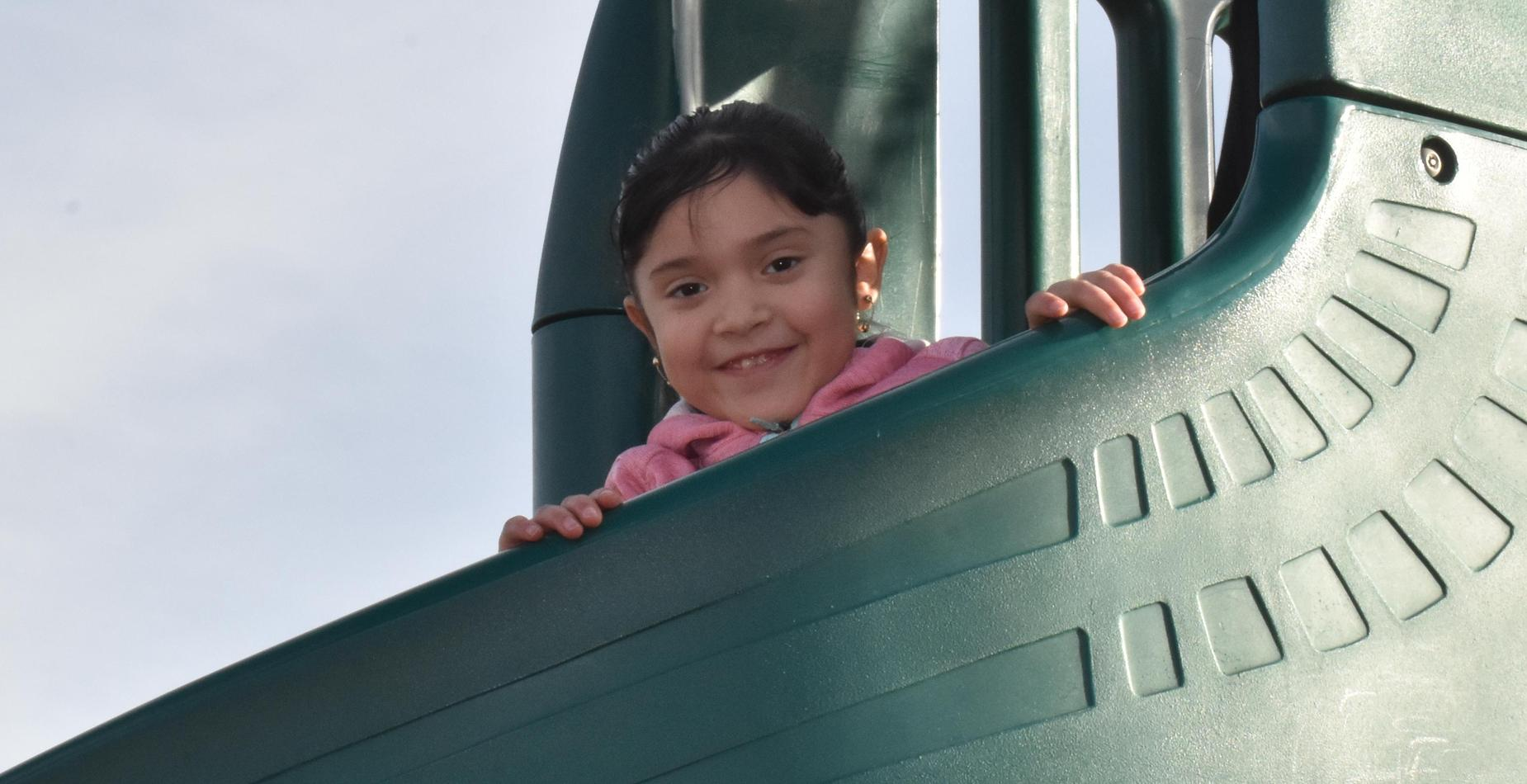 A little girl getting ready to go down the slide at recess time.