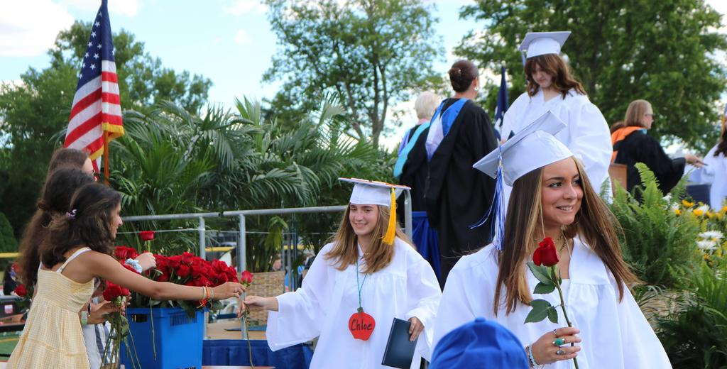 Photo of graduates receiving a rose after getting diploma