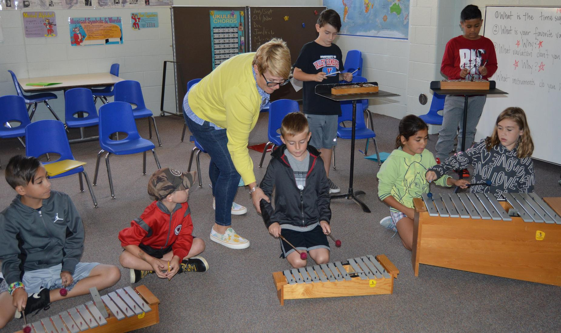 Girls and boys playing the xylophone in music class getting help from their teacher wearing a yellow sweater.