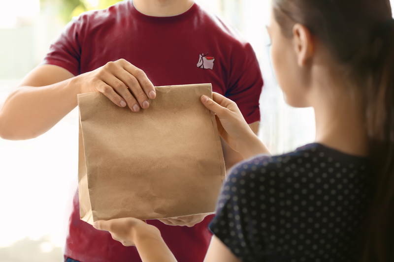 adult handing lunch sack