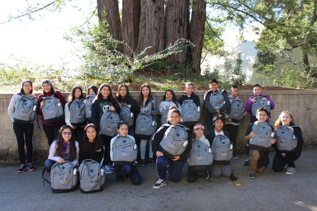 several student holding backpacks in front of a low cement wall with trees in the background
