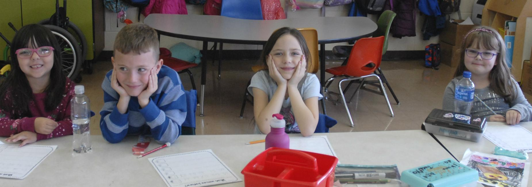 First grade students sitting at desks, smiling for camera