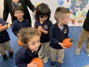 kids holding onto the pumpkins they just received
