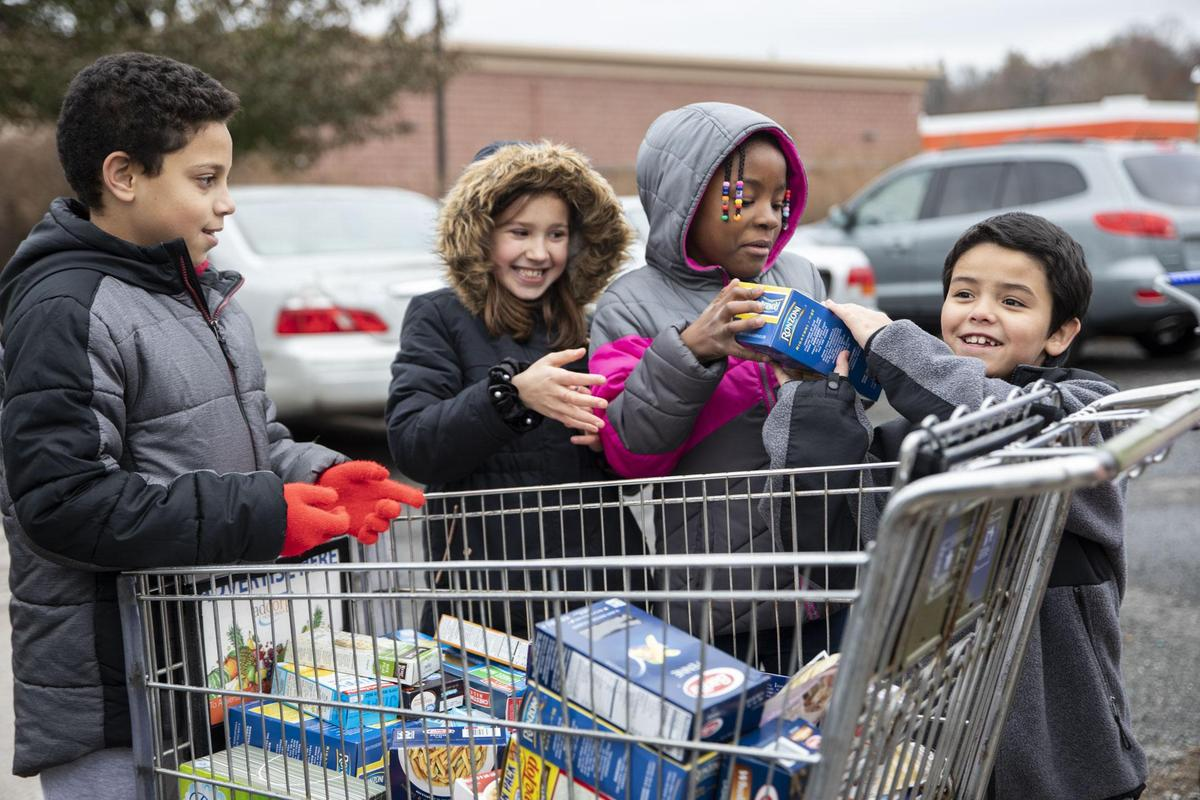Hop Brook students stack grocery cart with food for the food bank