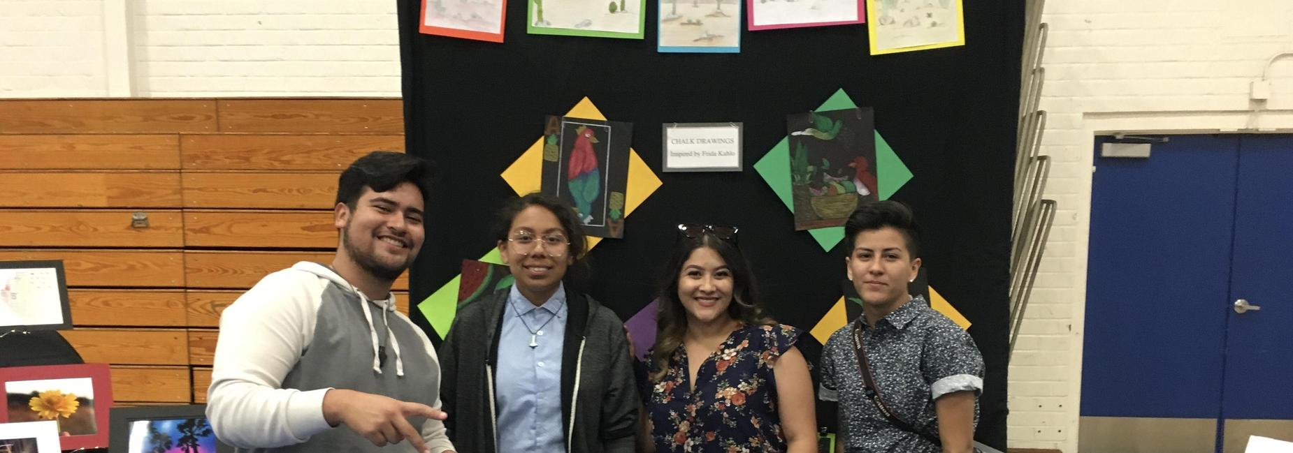 Students pose in front of student artwork