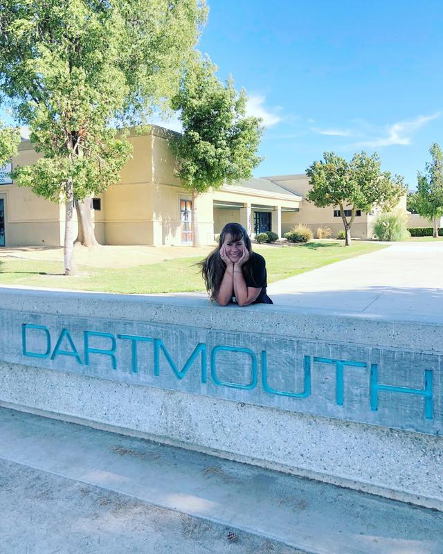 Lori Goodrich standing behind a Dartmouth block wall.