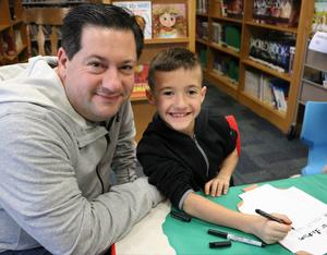 2nd grader tries his hand at calligraphy during Colonial Days at Wilson School.  Pictured here with his dad.