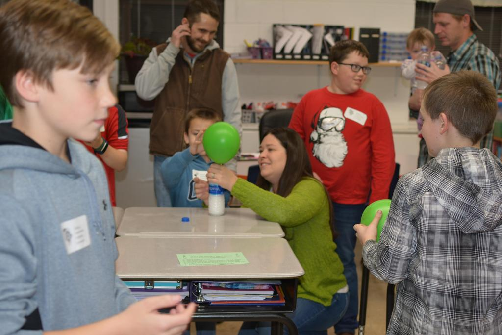 Students and families blow up balloon using a water bottle by adding water and baking soda