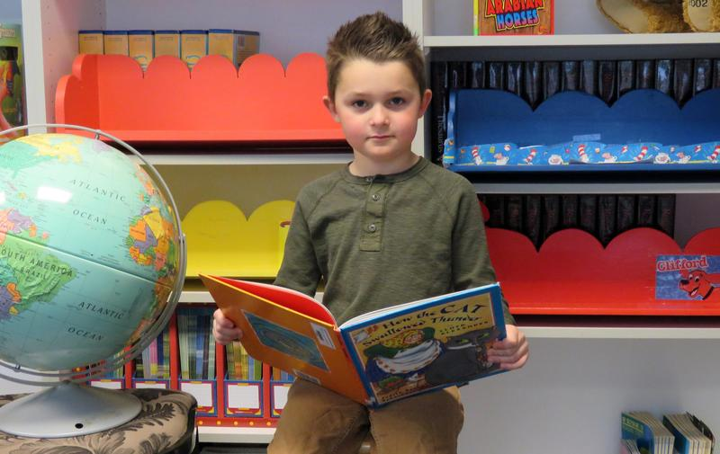 Kindergarten boys reads a book, surrounded by bookshelves and a globe.