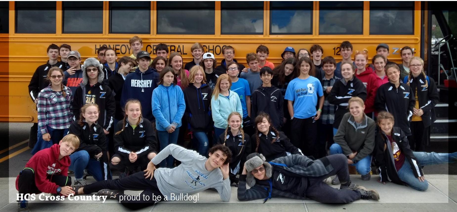 HCS Cross Country team posing in front of a Honeoye Bus