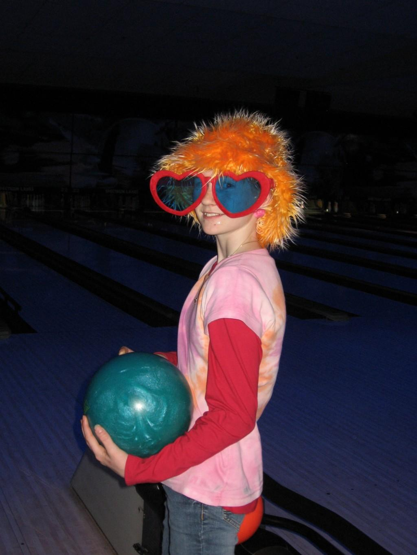 girl in oversize sunglasses prepares to bowl