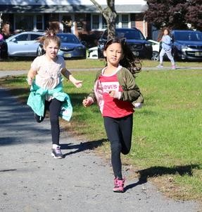 First grader Larkin Garcia (left) and second grader Zoe Mijaleski take advantage of sunshine and cool fall weather to run laps as part of the Recess Runners' Club at Washington School which encourages and rewards participants for every mile they complete over the school year.