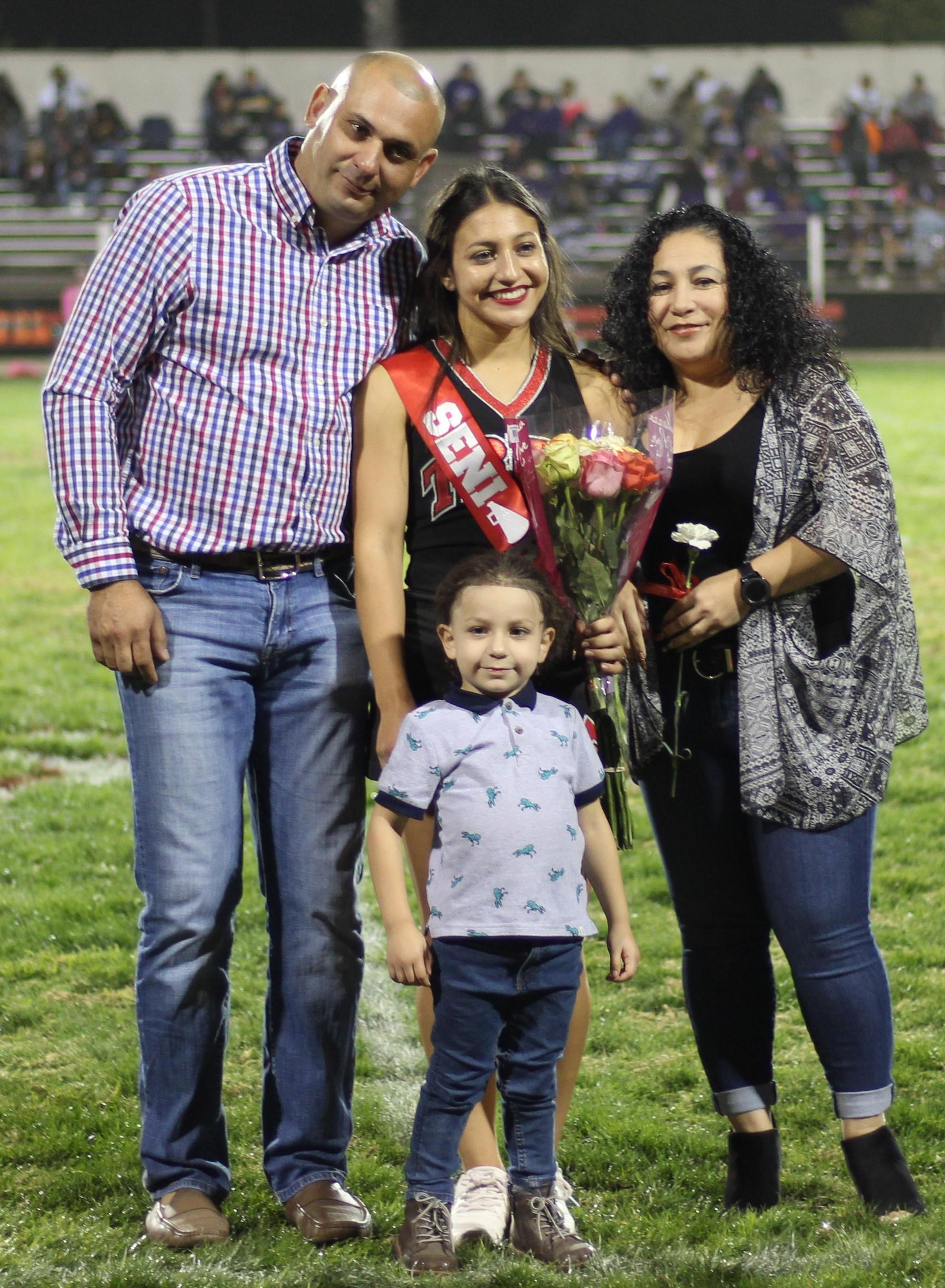 Senior cheerleader Bella Martinez and her escorts.