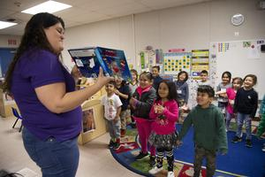 Carina Castellanos reads to preschool students