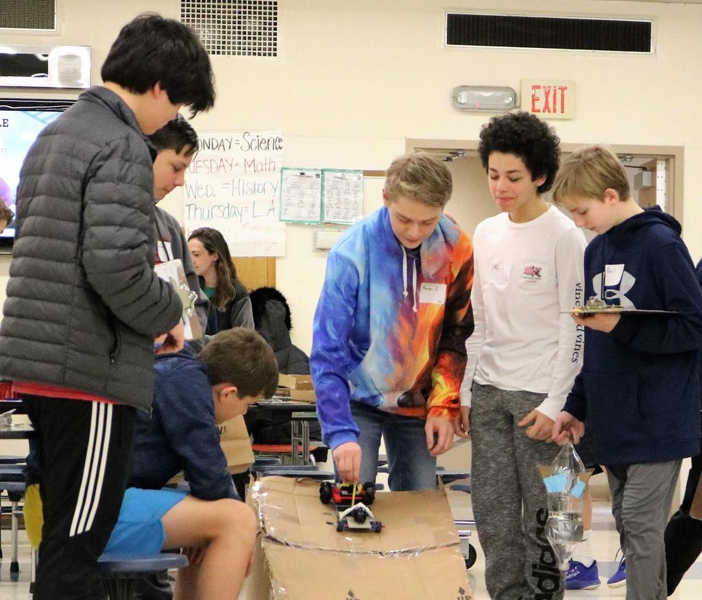 Photo of student ready to launch handmade car off ramp during Science Olympiad at Roosevelt Intermediate School, as other students look on.