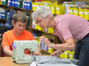 A third grader gets a little help with the sewing machine.