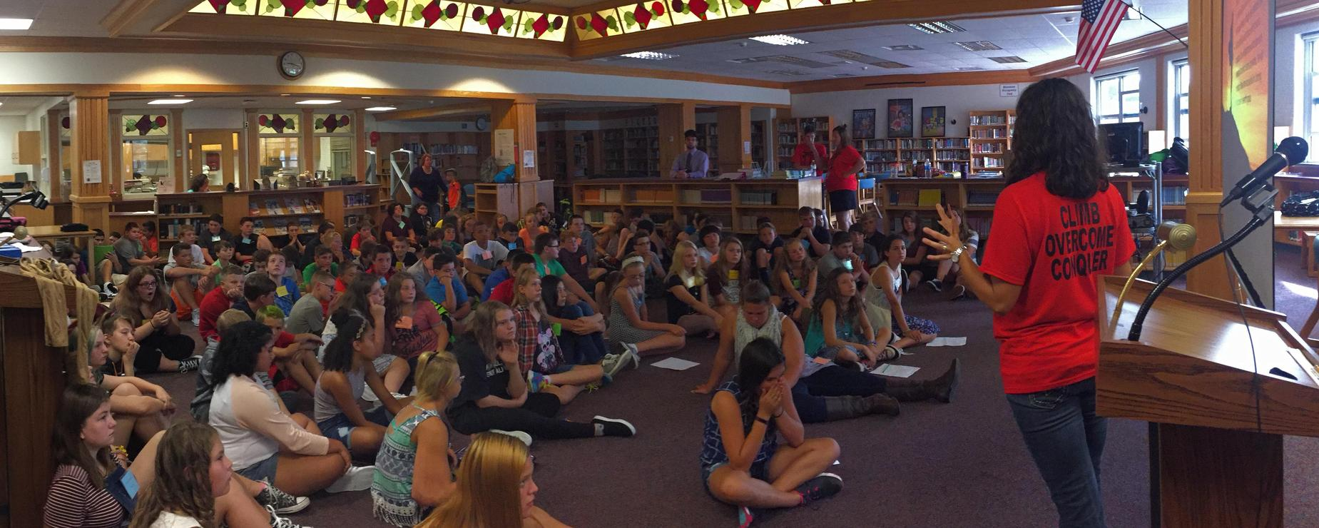 Assembly of students sitting on the library floor listening to the Club Overcome Counselor
