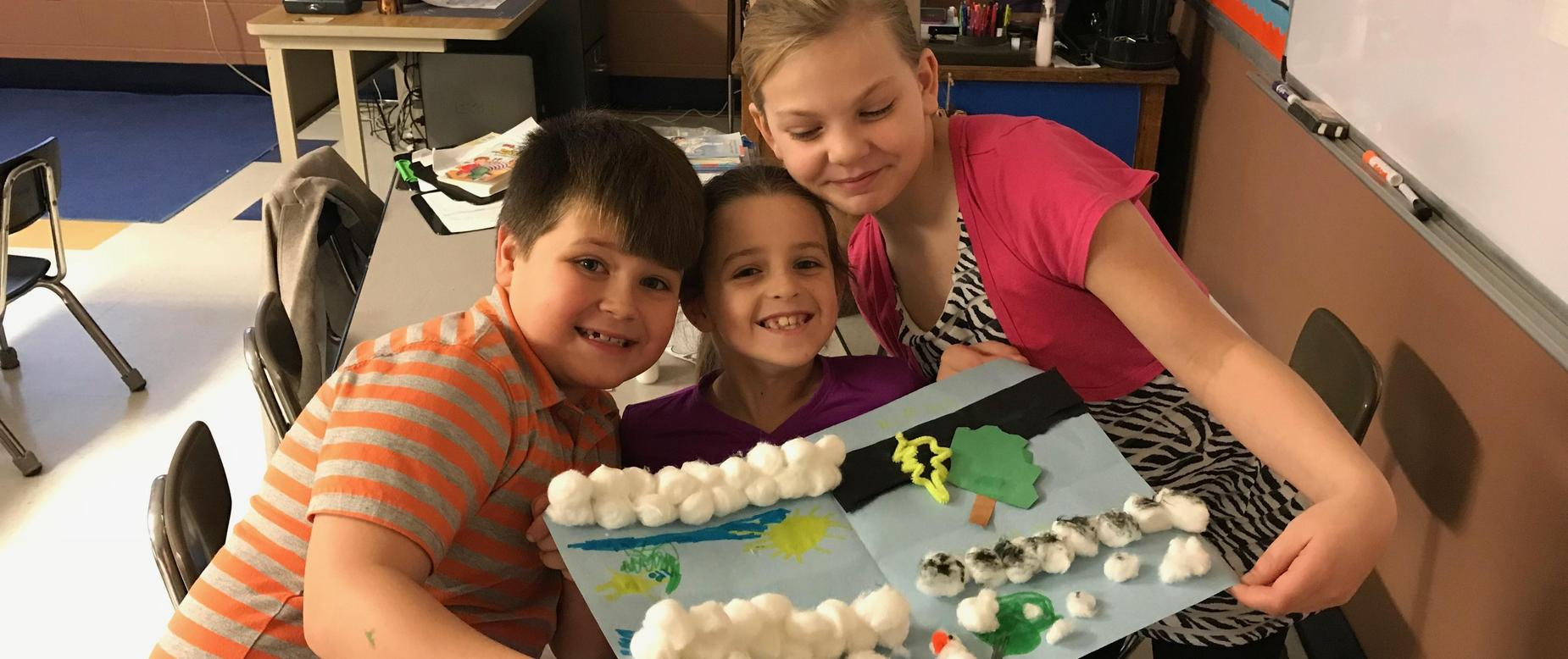 three elementary students hold up a project with construction paper and cotton balls