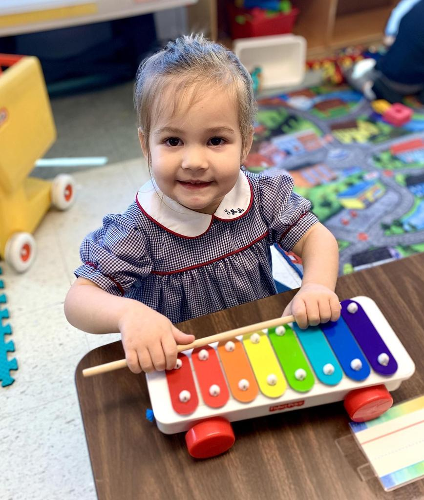 Girl playing with toy xylophone