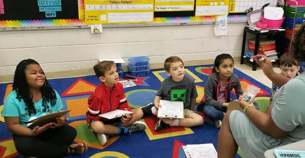 Second graders engaged in a language arts lesson with their teacher