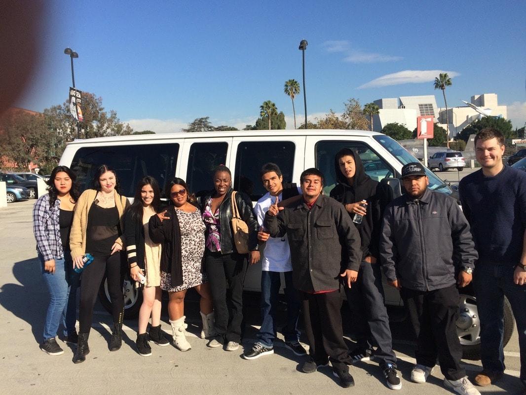 San Bernardino students pose in front of a van