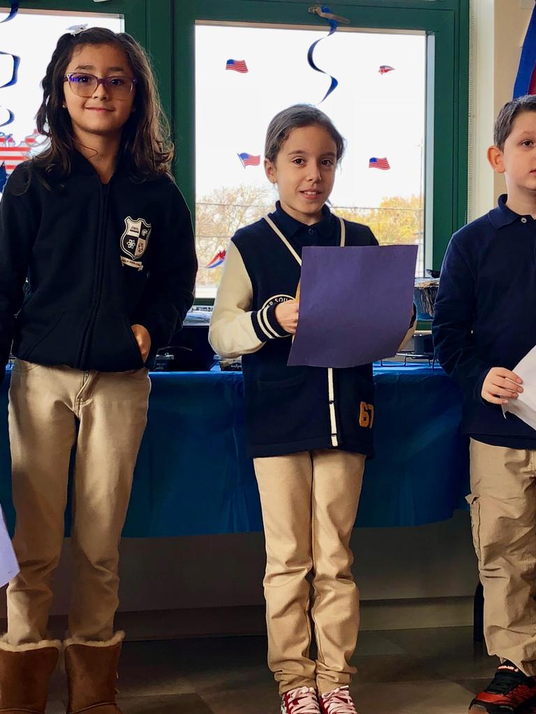 three children proudly standing ready to read their letters to the veterans