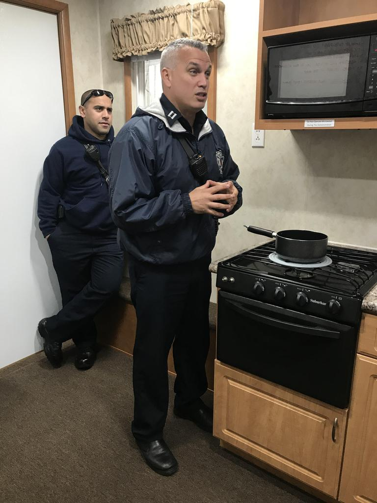 fireman in front of stove with pot on the stove talking about safety as a fellow fireman stands behind him