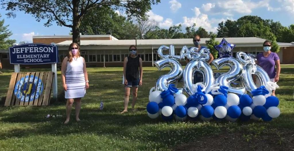 Photo of Jefferson teachers in front of balloons and signs for Grade 5 Clap Out Car Parade.