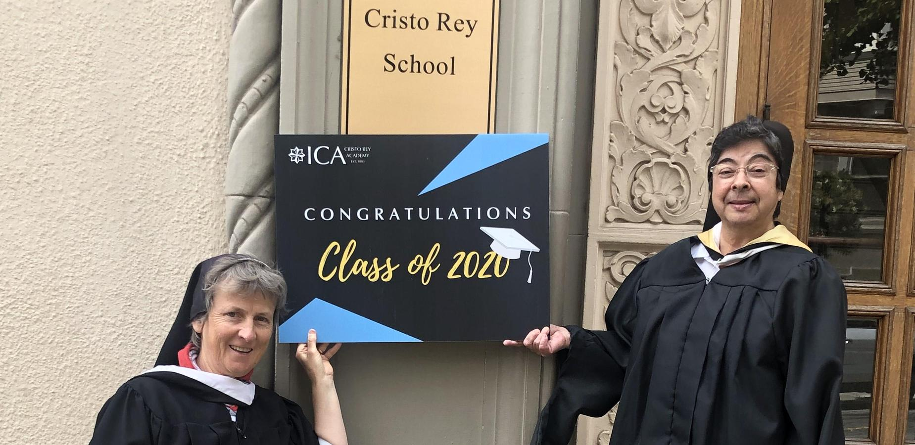 Sisters Lilly and Lisa Ann in from of ht eschool building holding a congratulatory sign for the class of 2020