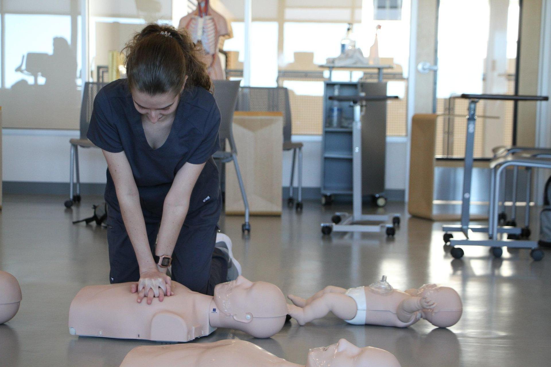 Girl practicing CPR in nursing class