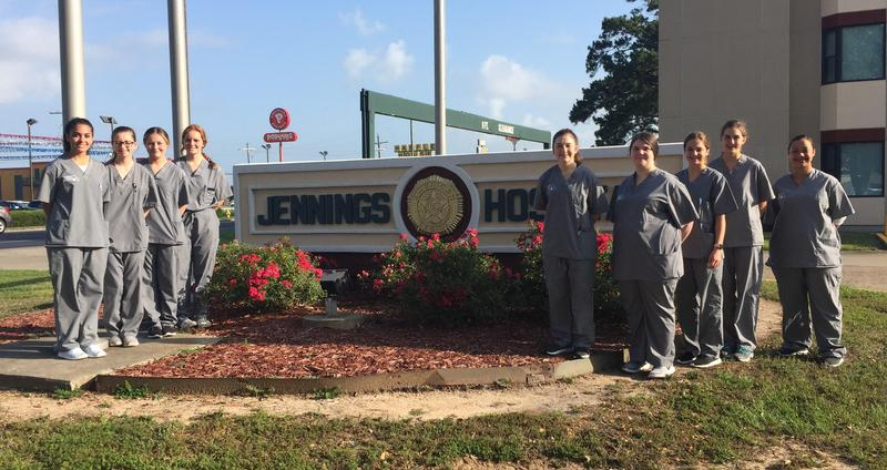 Students are standing next to the Jennings Hospital sign