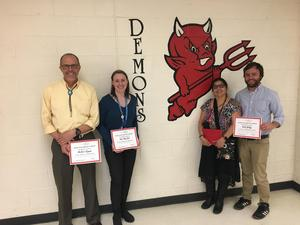 Photo of the four nominees for staff of the month standing with their certificates against a wall.