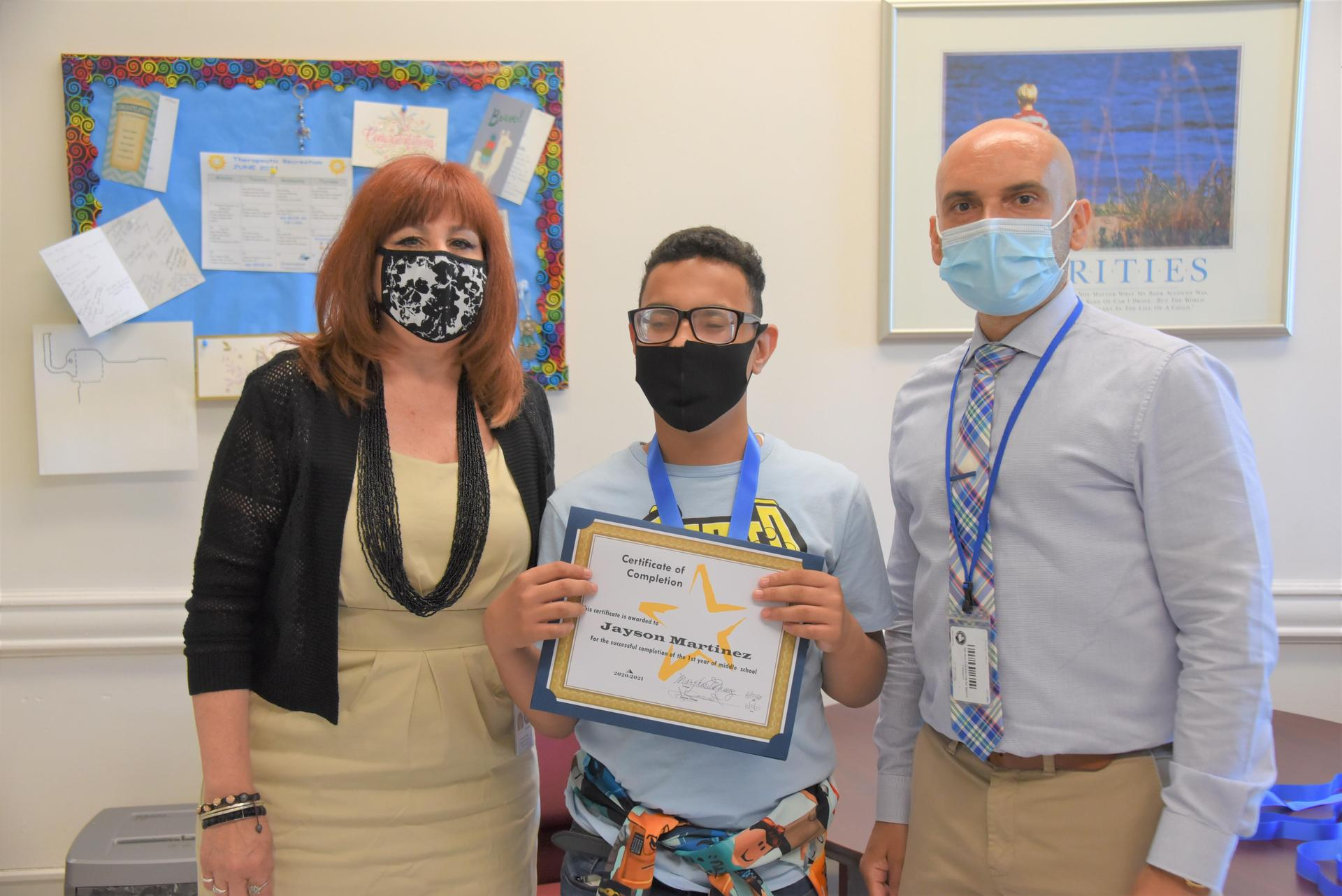The principal and the Assistant principal stand with a student getting an award in an office