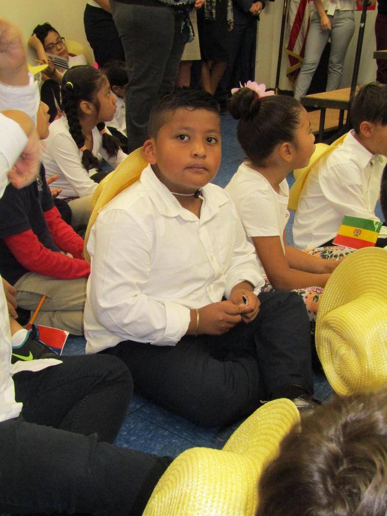 close up of a boy with a hat sitting on the floor waiting to perform