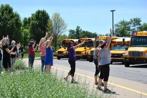 Teachers waving goodbye to students.