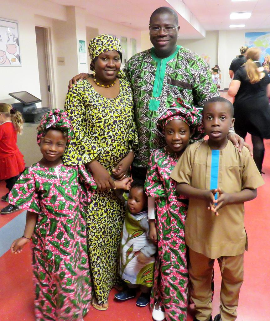 A family of six wears strikingly colorful full-length clothes representing their heritage