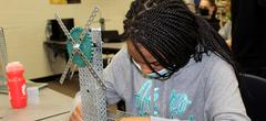PLTW girl bent over details while building machine