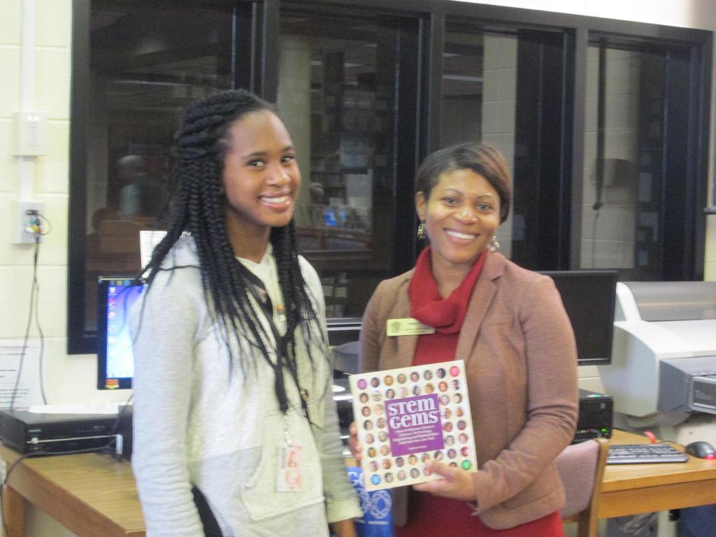 GaDOE Stem Consultant Felicia Cullars presents books to students.