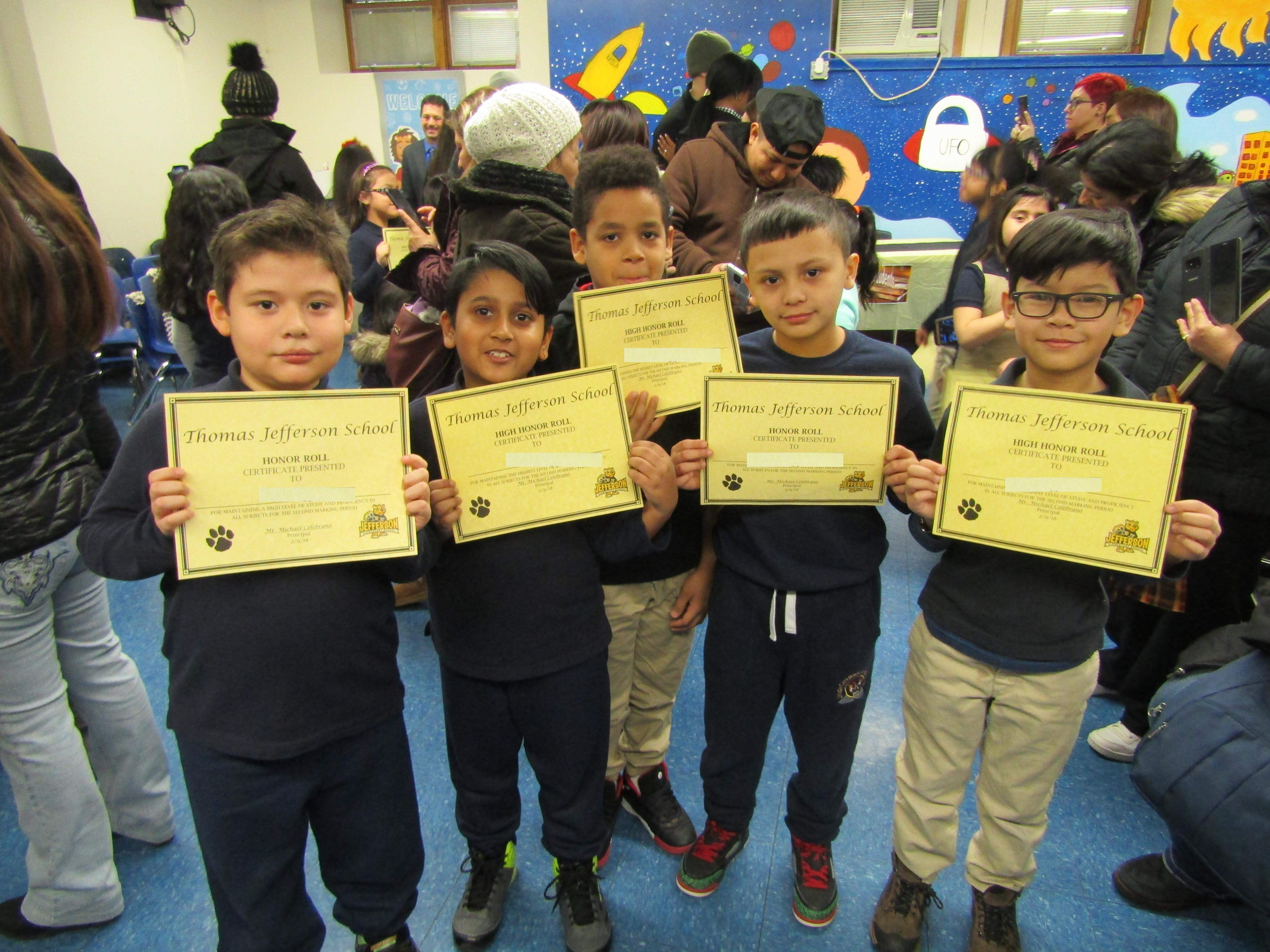 boys standing proudly showing off their certificates of honor