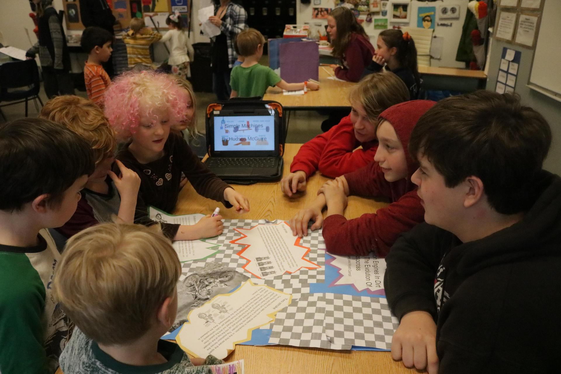 Students collaborate around a computer.