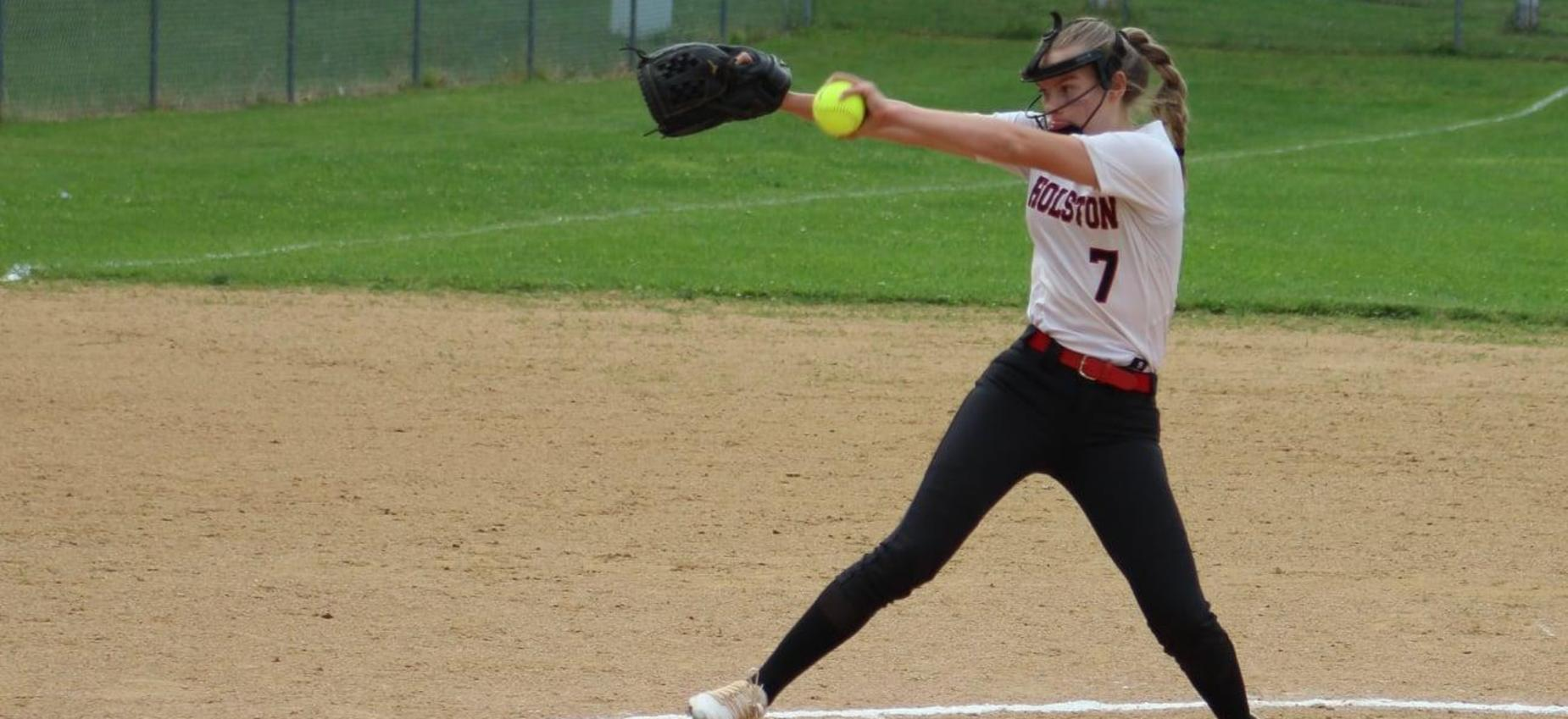 A softball player pitches the ball.
