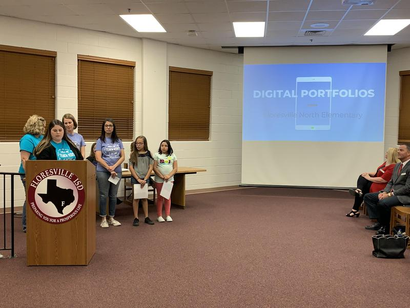 Students and teachers presenting about digital portfolios at a board meeting
