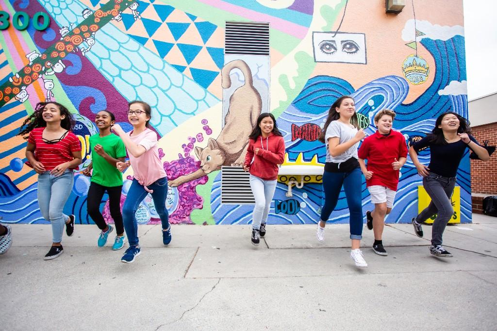Students running from mural