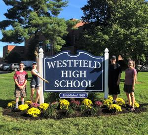 In preparation for last week's start of school, Westfield High School band members (L-R) Matt Ackerman, Sofia Lemberg, Sam Sherman and Madeline Ripper recently pitched in to help WHS PTSO landscape committee member Suzanne Sherman spruce up the WHS sign with brightly colored chryrsanthemums and other greenery.