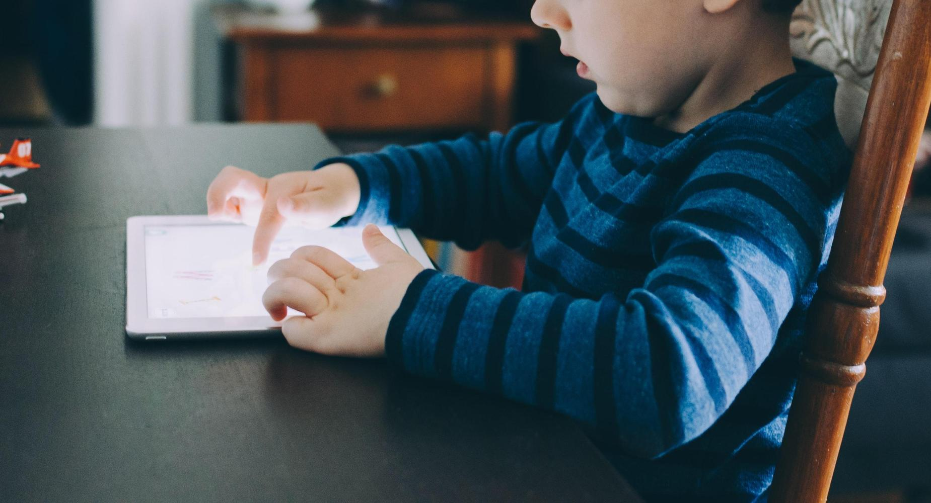 a young child sitting at a table uses an ipad