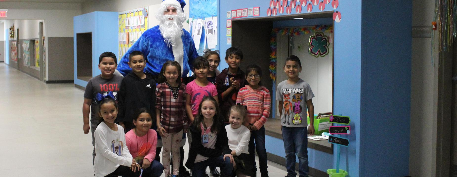 Excited Elementary Students with Blue Santa